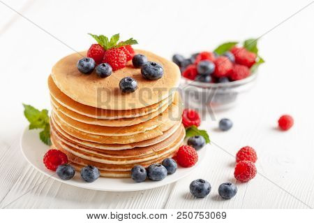 American Blueberry And Raspberry Pancakes With Coffee On White Wooden Table