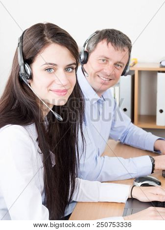 Side View Of Beautiful Young Businesswoman And Handsome Businessman In Headsets Using Laptops In Cal