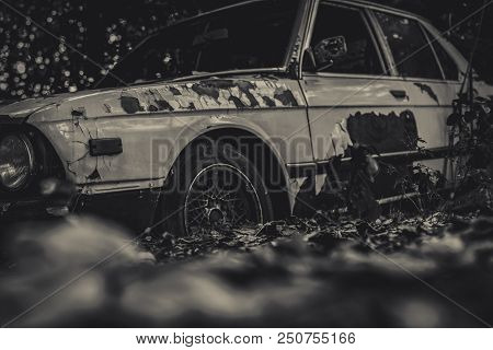 Old Wrecked Car In Black And White Scene. Abandoned Rusty Car In The Forest On Bokeh Background. Dec