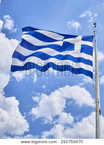Official flag of Greece waving on a cloudy sky.