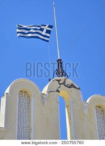 Flag Of Greece Waving On A Blue Sky.
