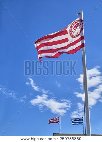 Athens, Greece - June 29, 2018. Flags of Olympiacos Football Club team and Greece waving on a blue sky.