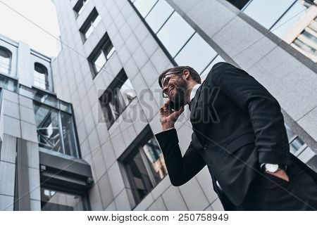Confident Business Expert. Low Angle View Of Good Looking Young Man In Full Suit Talking On The Phon