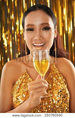Gorgeous Lively Asian Female In Bright Sequin Top And Earrings With Sparkling Golden Glitter On Lips