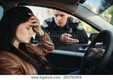 Male cop in uniform check female driver on road