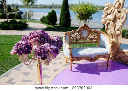 Chair On Wedding Ceremony Arch With Gold Luxury Frame And Purple Flower And On Riverside. Bride And