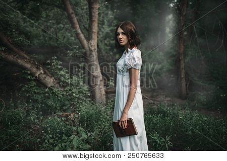 Female victim in white dress holds book in hand