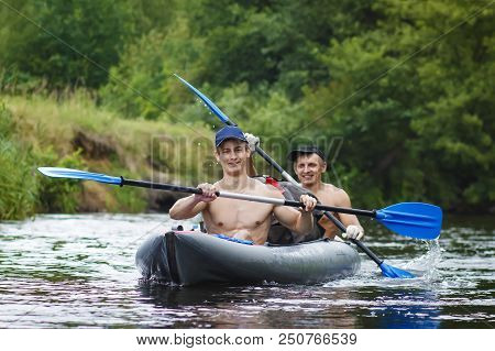 Rowers Are Rafted Along River In A Kayak. Two Friends Are Swimming In Boat On River And Rowing Oars