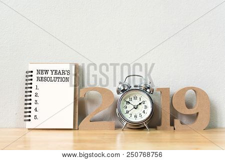 New Year's Resolution On A Notebook And Wood Number 2019 With Clock On Wood Table And Copy Space