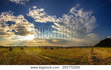 Dramatic Sunset Over A Fields. Straw Bales In Fields Farmland With Blue Cloudy Sky At Harvesting Tim