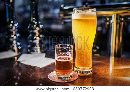 Light Beer In A Beer Glass And Dark Beer In A Small Glass Lighted With Warm Light On A Bar Counter