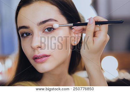 Pink Lips. Green-eyed Good-looking Woman With Pink Lips Using Eye Shadows While Putting Makeup On