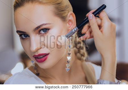 Finishing Makeup. Good-looking Woman With Red Lips Wearing Nice Earrings Finishing Her Makeup