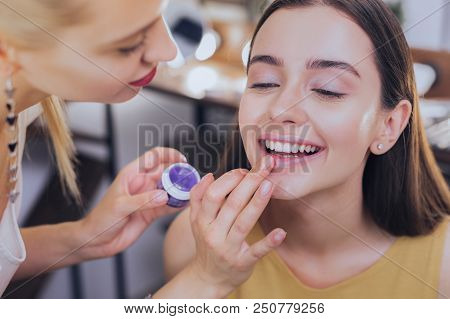 Nice makeup. Beautiful beaming woman with nice makeup feeling joyful while sitting in beauty saloon poster