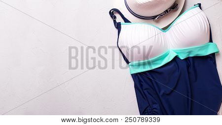 Beach Accessories  Swimsuit And Hat On Textured Background. Vacation, Summer Concept. Top View. Plac