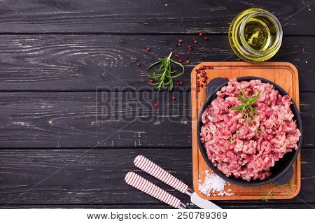 Raw Minced Meat In Bowl  With Ingredients For Cooking On  Black Table. Selective Focus. View From Ab