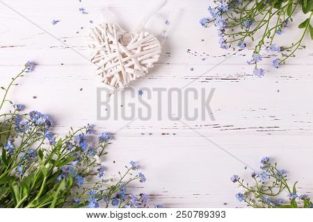 Frame  From  Blue Forget-me-nots Or Myosotis Flowers And Heart On  White Wooden Background. Floral S