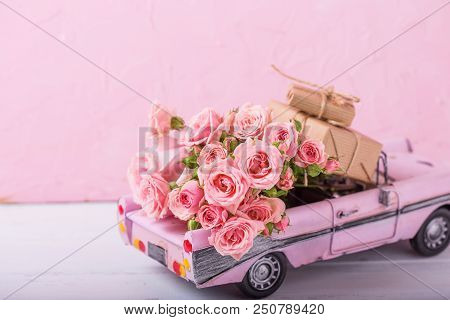 Retro Car Toy With Pink Roses And Wrapped Boxes With Presents  Flowers Against  Pink Textured  Wall.