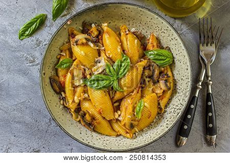 Pasta Conchiglioni With Mushrooms In A Vintage Bowl On A Dark Stone Or Concrete Background. Top View