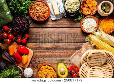 View From Above Of A Wooden Rustic Table With Several Ingredients For Cooking And Filling Arepas, Ty
