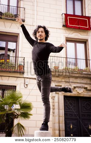 Male Dancer Performing Pirouette. Urban Background. Nomal Expression