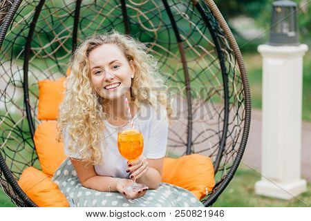Adorable curly young female with curly bushy hair, holds glass of orange cocktail, poses in hanging outdoor chair, expresses positiveness, has pleasant talk with interlocutor. Leisure concept poster