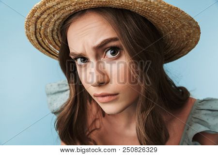 Close up portrait of a curious woman in dress and summer hat looking closely at camera isolated over blue background