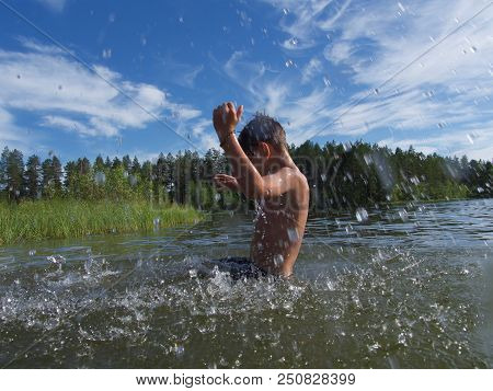 Kid Splashes Of Water Around A Swimmer Diving Into The Water. Kid Excited About Swimming. The Concep