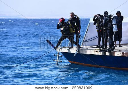 Egypt - June 15, 2014: Scuba Divers Jump From Boat In Blue Sea Water On Sunny Day. Diving Destinatio