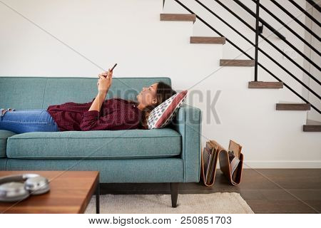 Side View Of Woman Lying On Sofa At Home Using Mobile Phone