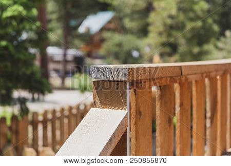 Wooden Deck Railing, Showing Some Signs Of Wear, In A Summer Day Forest Setting.