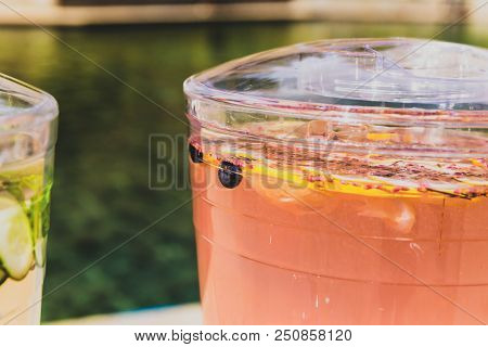Fresh Fruit Floats In A Pink Beverage Inside A Plastic Pitcher (or Jug). Pool In Background. Summer