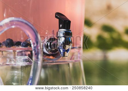 Chrome And Plastic Pitcher Spout On A Clear, Plastic Pitcher Containing Pink Drink With Blueberry Fr