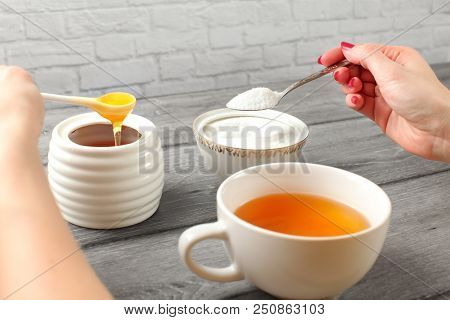 Young Woman Hands, Holding Spoon Of Sugar And Honey In Other Hand Deciding What To Put In Her Tea. A