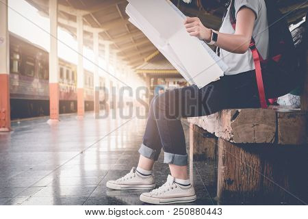 Asian Woman Sitting Planning Vacation Trip With Map At The Train Station.vintage Filter Effected .