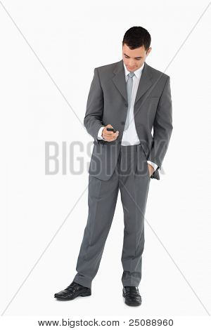 Young businessman writing textmessage against a white background