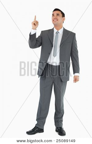 Businessman pointing and looking upwards against a white background