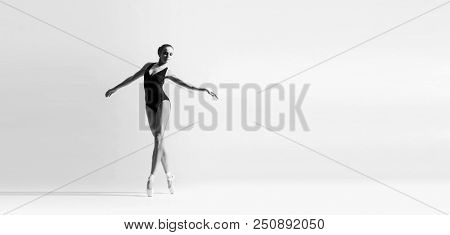 Graceful ballerina dancing in art performance. Young and beautiful ballet dancer.