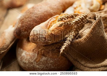 Heapf Of Fresh Baked Bread With Burlap And Ears Of Wheat