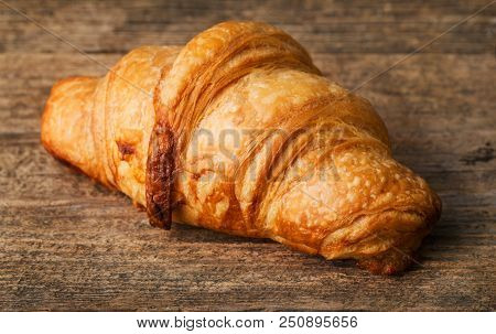Single Fresh Croissant On The Wooden Background