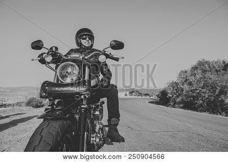 Black And White Portrait Of Man With Black Helmet, Jacket And Sunglasses Standing On A Classic Ameri