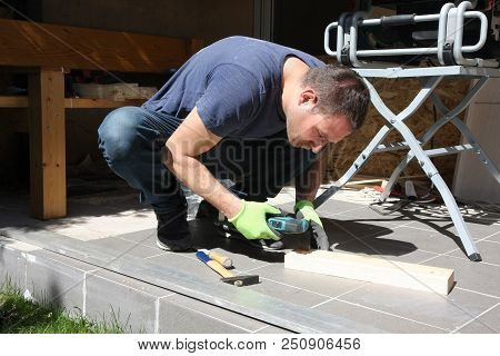 A Man In The Yard Enjoys The Processing Of Wood