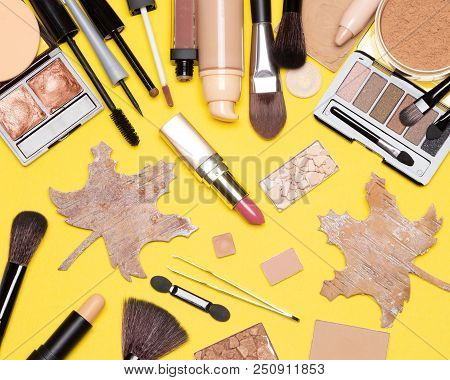 Autumn Makeup Flatlay. Various Make-up Products Brown And Golden Shades With Maple Leaves Made Of Ba