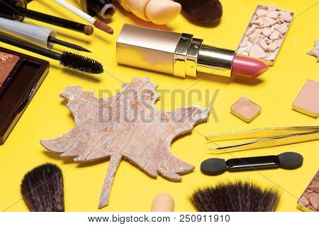 Autumn Makeup. Make Up Products And Accessories With Maple Leaf Made Of Bark On Yellow Background. C