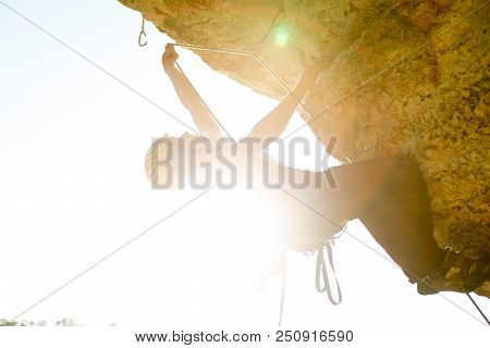 Picture Of Male Climber In Helmet Clambering Up Cliff. Sunflare Effect.