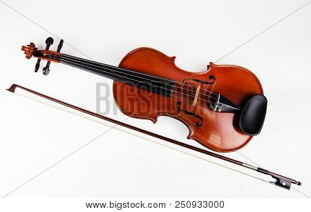 Closeup The Classic Violin Put Beside Wooden Bow On White Background,show Size And Body Of Violin.