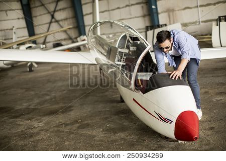 Handsome Young Pilot Checking His Ultralight Airplane Before Flight