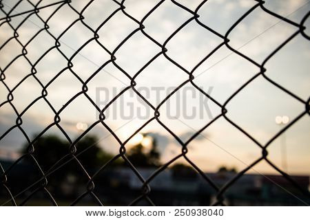 Limitless boundaries concept.  Sunrise sunset through chain link fence in bokeh background, wallpaper.