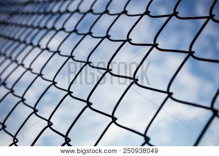 Limitless boundaries concept.  Sky through chain link fence in bokeh background, wallpaper.