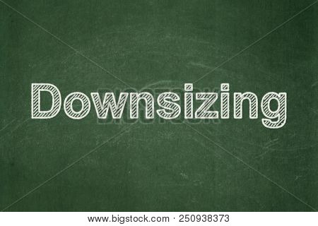 Finance Concept: Text Downsizing On Green Chalkboard Background